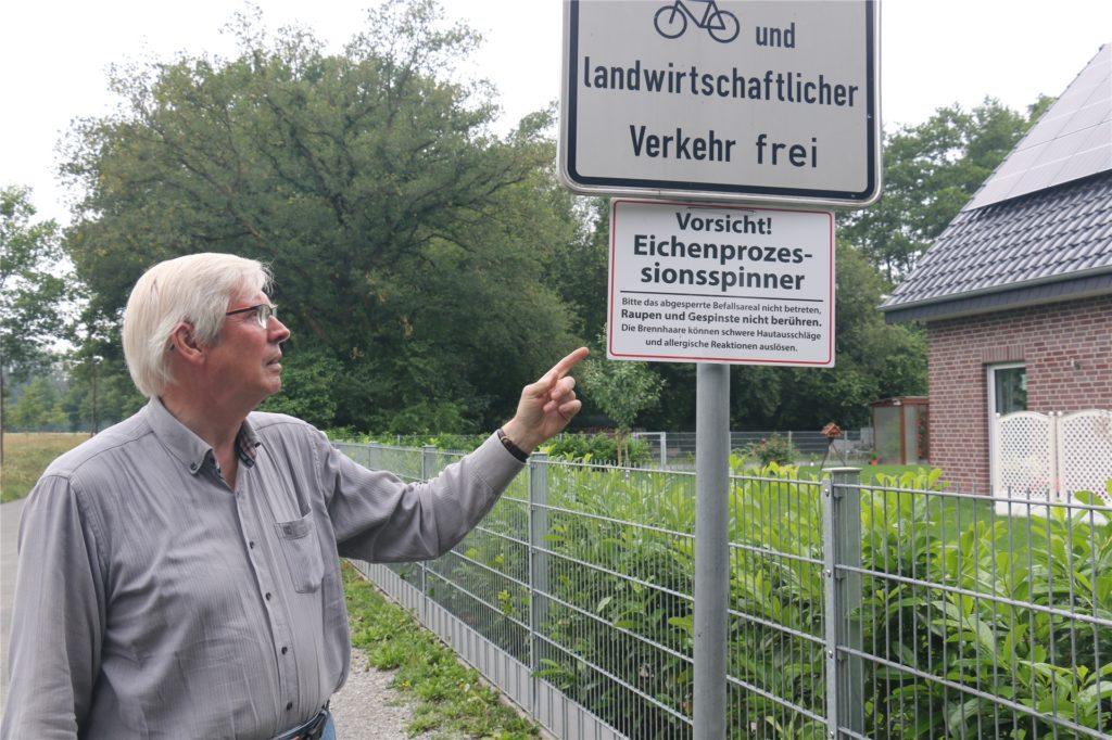 Horst Löscher zeigt ein Hinweisschild, das am Eingang der Allee hängt. Die Schilder werden wohl auch nach der Behandlung der Bäume noch zu sehen sein.