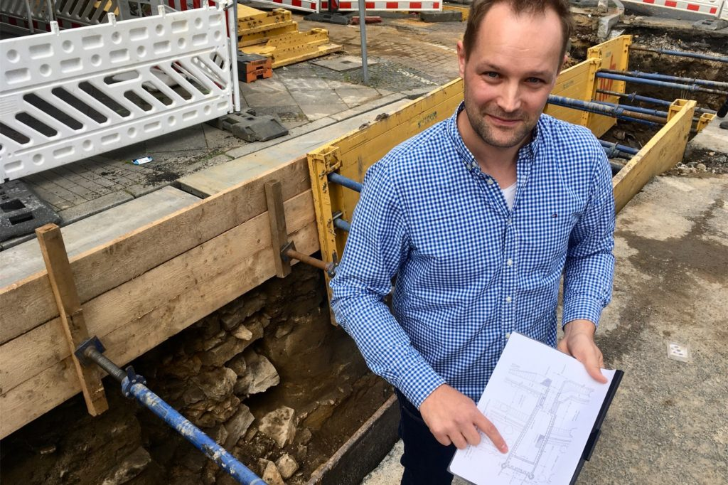 Stadtarchäologe Ingmar Lutter zeigt vor der Grabungsstelle, welcher Teil des Osterntores freigelegt wurde: eine Quermauer des Vorwerks.