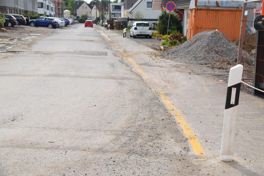 Dauerärgernis der Anwohner: die Straße zum Erdbeerfeld. Zwar gibt es mittlerweile einen angegossenen und markerten Fußweg. Der marode Zustand der Straße lässt aber die Neubauten wackeln. Im Juli will die Stadt eine provisorische neue Fahrbahndecke aufziehen.