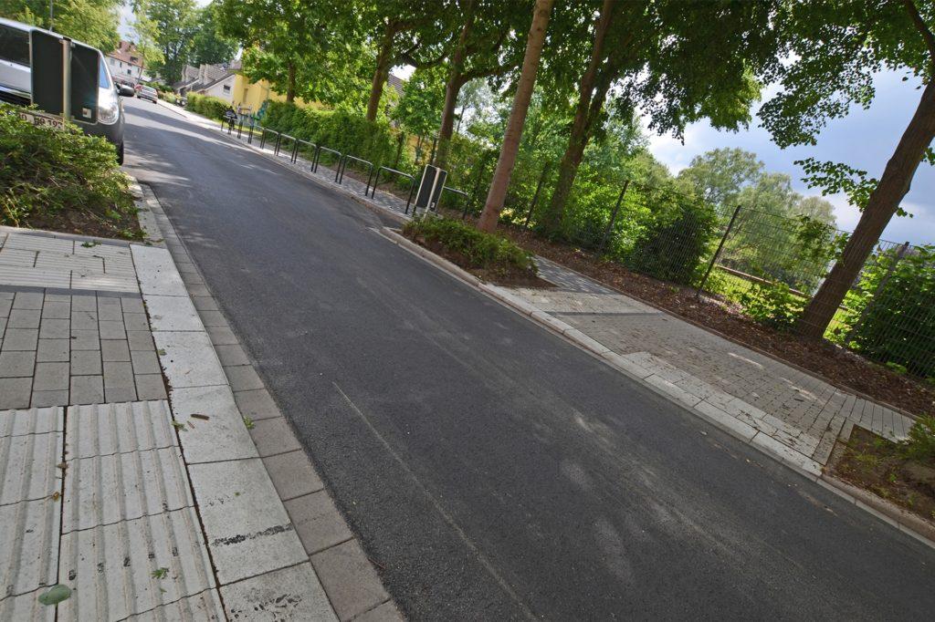 Aufwendig wurde die Querungshilfe nördlich der Schuleinfahrt saniert und barrierefrei ausgestattet. 30 Meter Fußweg auf der Seite der Schule erhielten ein schwarz-weißes Pflaster als Schulwegsmarkierung.
