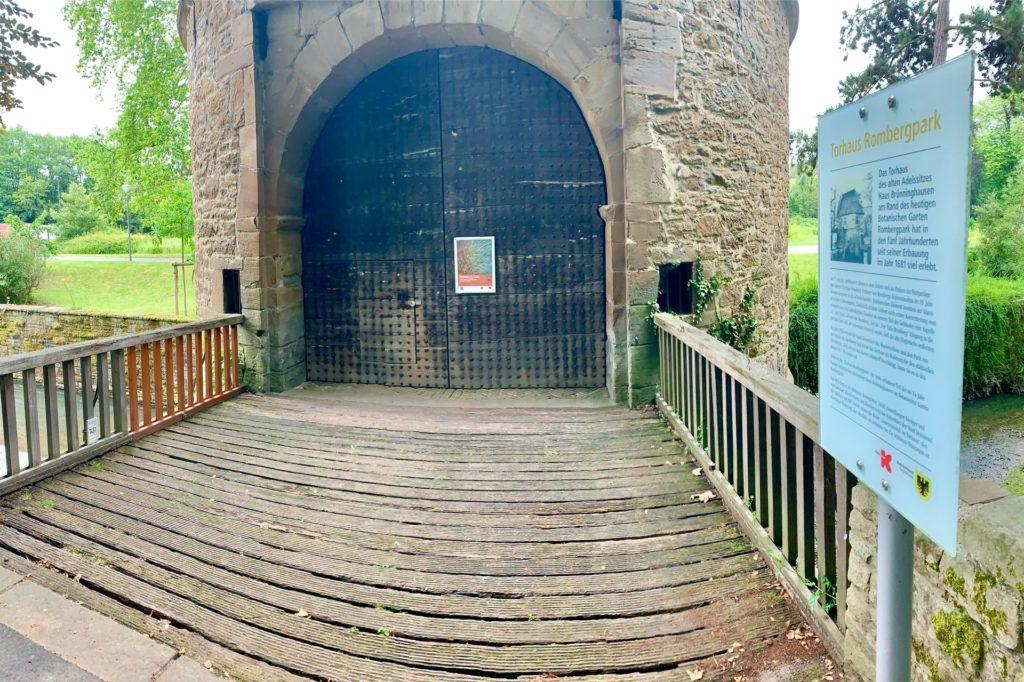 Gut zu erkennen ist, dass die Bretter der Holzbrücke in die Jahre gekommen sind.