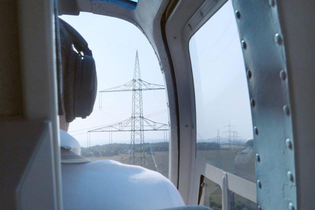 Pilot im Tiefflug neben Stromleitungen