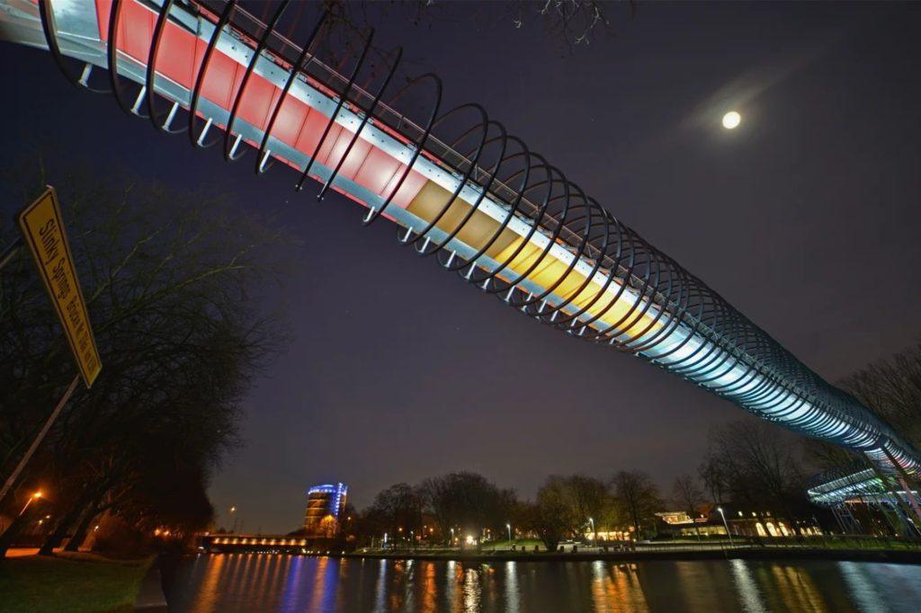 """""""Slinky springs to Fame"""" heißt die ungewöhnliche und in den Abendstunden beleuchtete Brücke, die sich in Oberhausen über den Rhein-Herne-Kanal windet."""