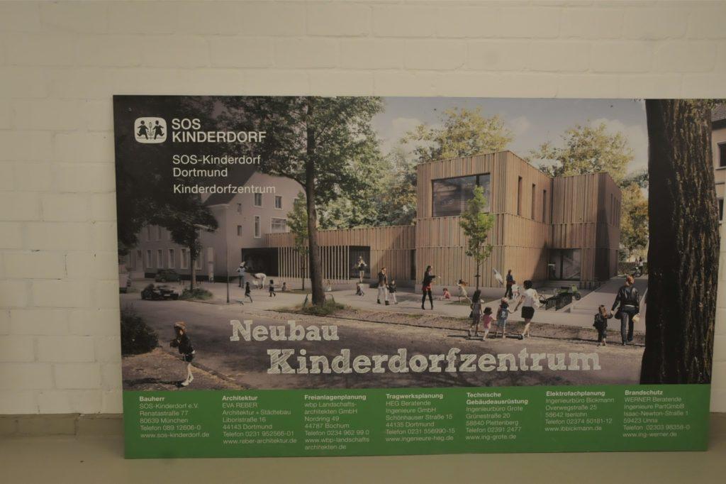 Dieses Plakat zeigt den Holzbau der Kita Krönchen, die zum neuen SOS Kinderdorf Dortmund gehört. Im Juni sollte öffentlichkeitswirksam mit einer Feier eröffnet werden.