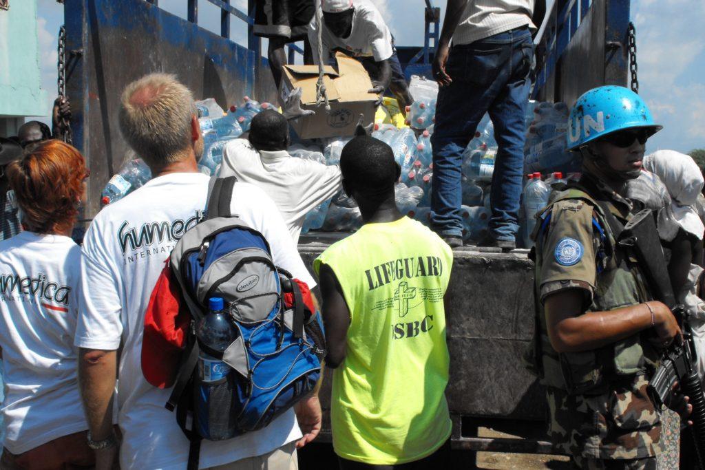 Nina Wöhrmann im Jahr 2008 in Haiti. Das Land war von drei Hurricanes hintereinander heimgesucht worden, an die in Not geratenen Menschen wurden Lebensmittel ausgeteilt. Unter Bewachung von bewaffneten UN-Soldaten,