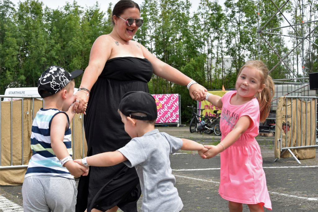 Sophie (4), Louis (3), Nick (4) und Nathalie Skarda (v.r.n.l.) tanzen zur Musik in ihrer Strand-Launch.