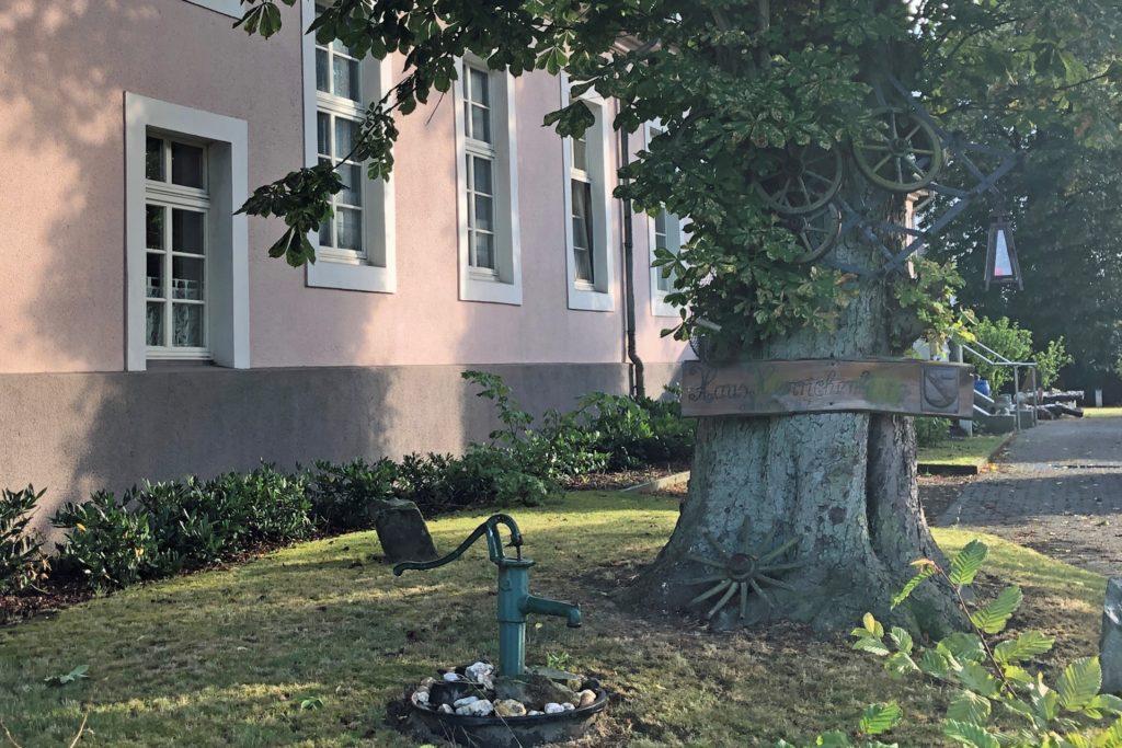 Ein Holzschild an einem Baum vor dem Haus weist auf Namen und Baujahr von Haus Henrichenburg hin.