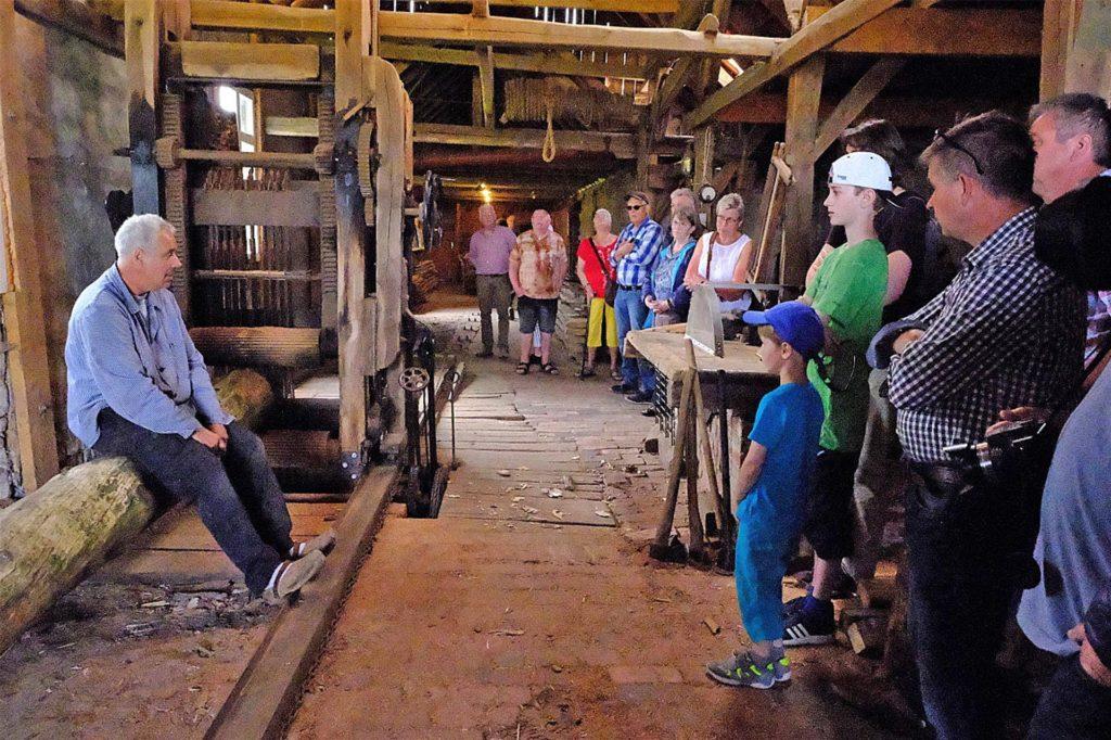 Beim Mühlentag: Dieter Gehling (links) erklärt den Besuchern die Funktionsweise des Sägegatters und schneidet dann einen Baumstamm zu Brettern.