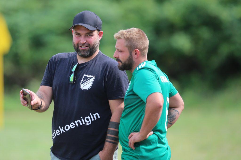 Hatte während des Spiels Zeit für einen Blick auf das Handy mit einem seiner Einwechselspieler: Victoria-Trainer Danny Jordan (l).