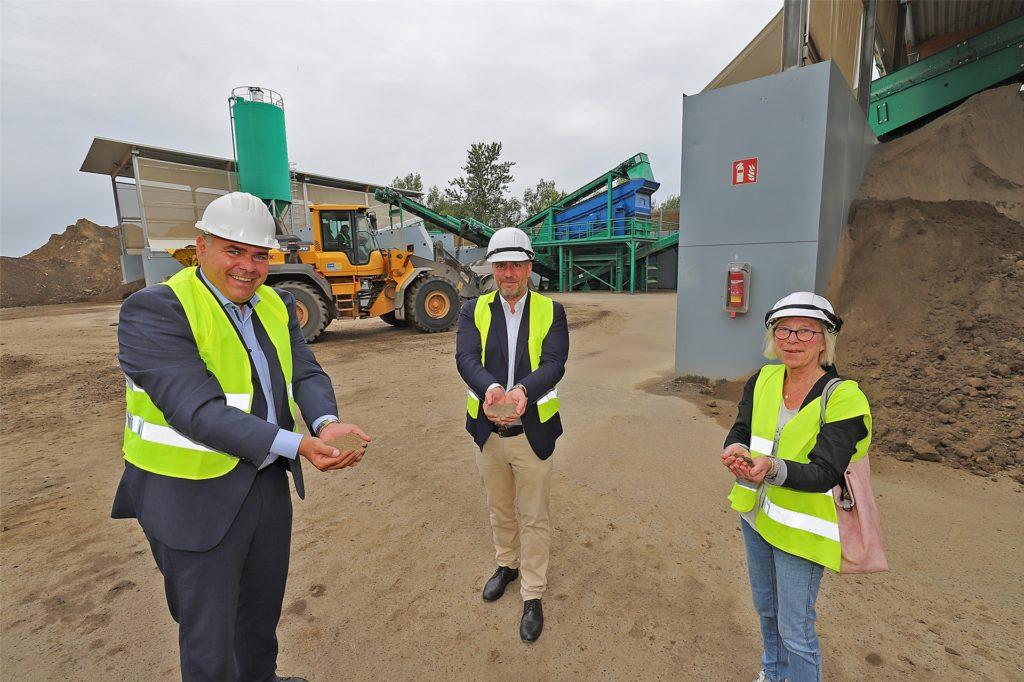 Der Selmer Bürgermeister Mario Löhr (l.) erkundigt sich als Verwaltungschef über eine mögliche Kooperation mit dem Sandwerk in Kamen, an der die GWA zu 50 Prozent beteiligt ist. Geschäftsführer Andreas Gérard und Aufsichtsratsmitglied Brigitte Cziehso (SPD) zeigen ihm, wie aus deponierter Muttererde Sand produziert wird.