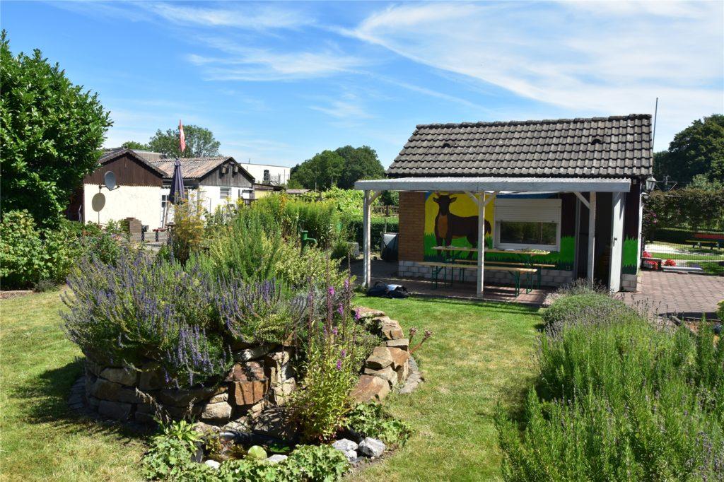 Der Schulgarten mit der großen Kräuterspirale und dem dem Gartenhaus im Hintergrund.