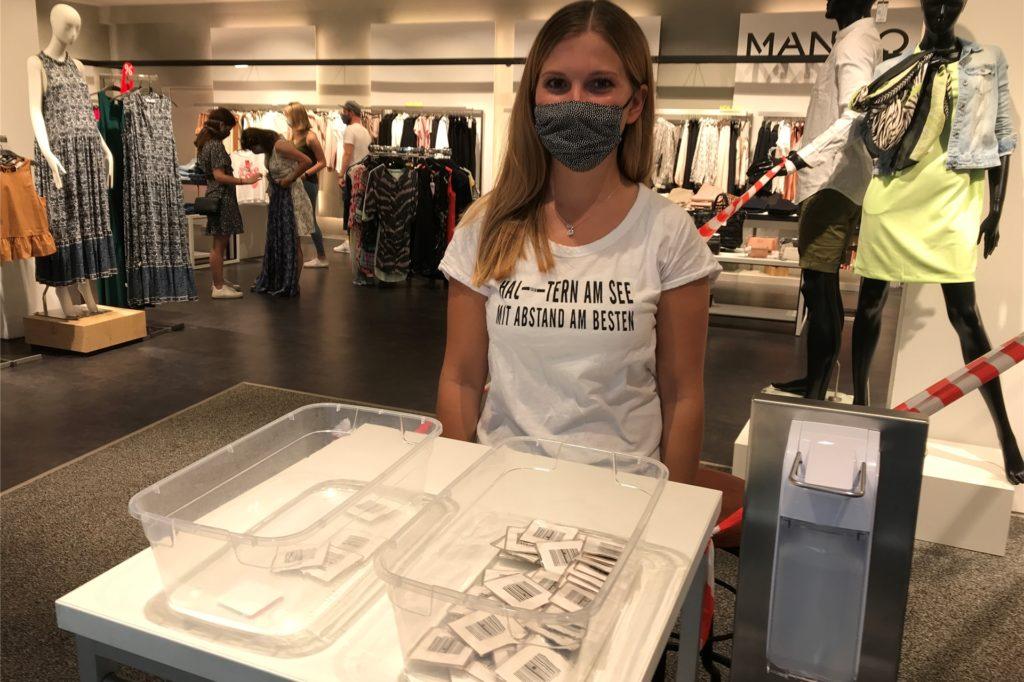 Bei Mode Heckmann verteilte eine Mitarbeiterin eingeschweißte Etiketten am Eingang, um die Zahl der Kunden zu kontrollieren.