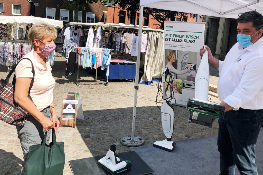 Marktbesucherin Monika Efing und Staubsauger-Händler Friedhelm Mesken freuen sich, dass der Krammarkt seine Coronapause beendet hat.
