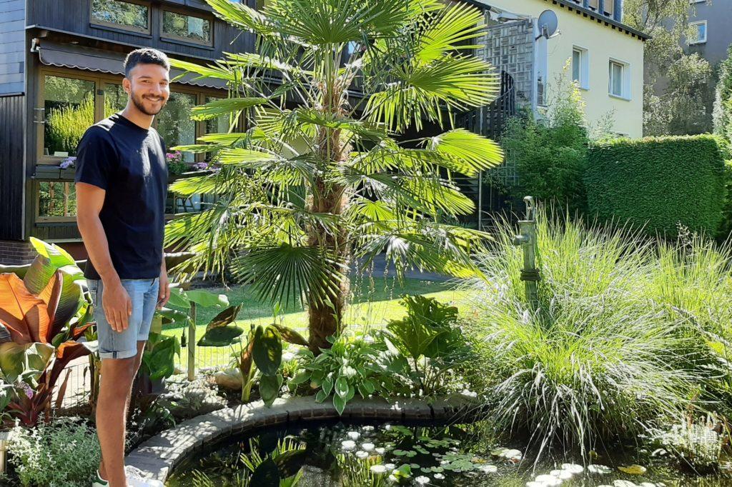 Den Teich hat schon sein Opa angelegt, nun kümmert sich Robin Gordon darum. Die Palme rechts neben ihm, hat er erst vor wenigen Jahren gepflanzt – seitdem ist sie schon etwa doppelt so groß geworden.