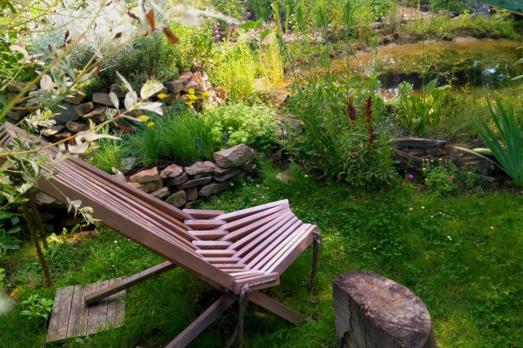Der Holzstuhl am Teich ist einer der Lieblingsplätze der Familie.