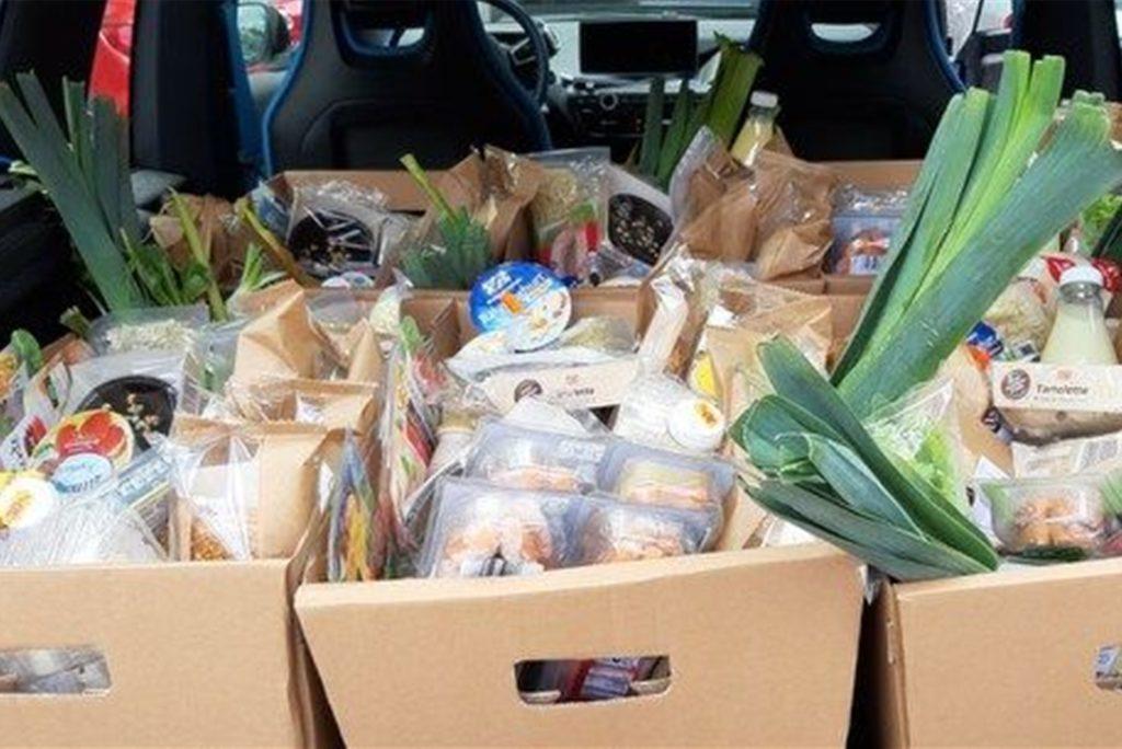 Mitarbeiter der Tafel stellen Lebensmittelpakete für Bedürftige zusammen und liefern sie dann in Autos aus.