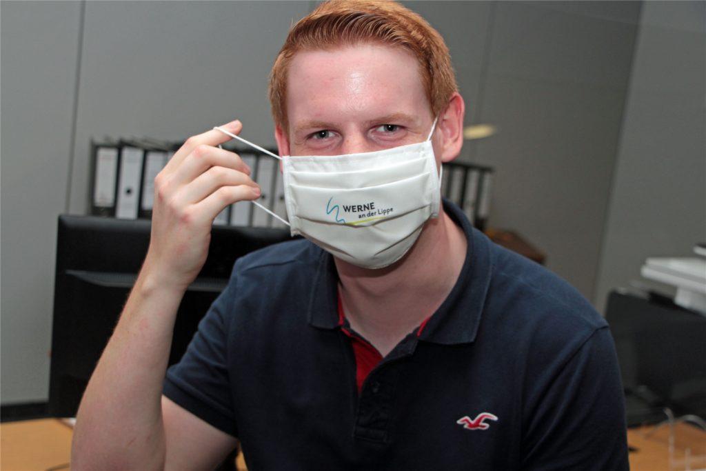 Verwaltungs-Auszubildender Robin Nolting zeigt die Stoffmaske mit dem Stadt-Logo, die alle Wahlhelfer als Dankeschön erhalten sollen.