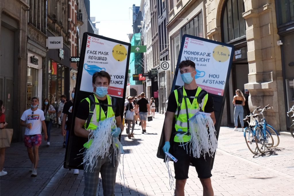 In Amsterdam werden Mundschutz-Masken an Passanten verteilt.