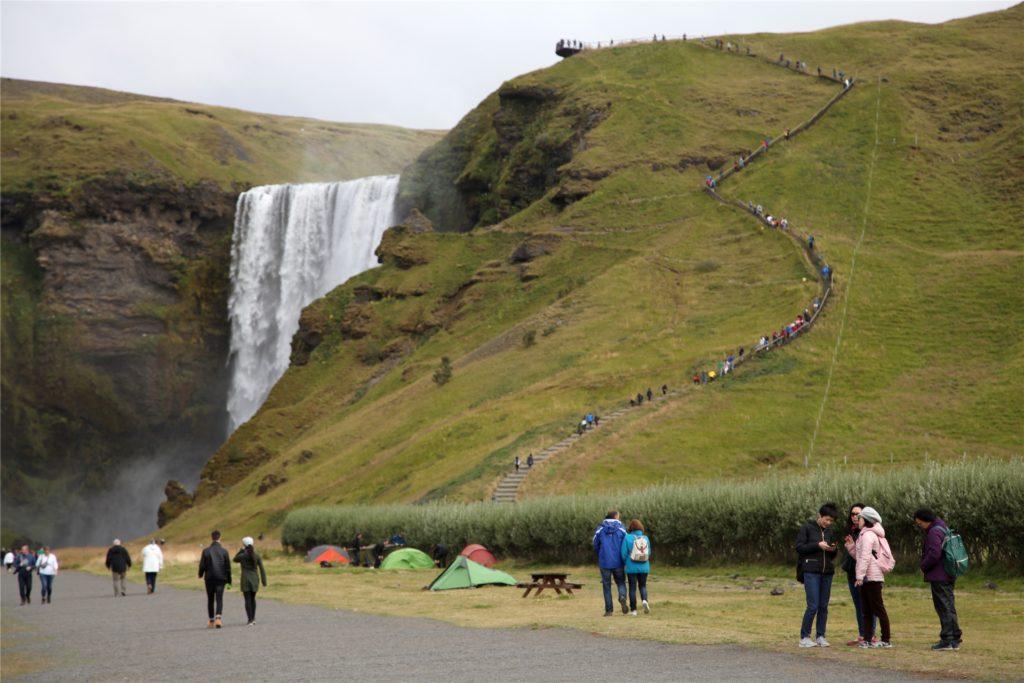 Touristen spazieren am Wasserfall Skogafoss vorbei. Jahrelang sind die Touristenzahlen auf Island in die Höhe geschossen. Jetzt sollte sich all das stabilisieren. Stattdessen kam Corona - mit immensen Folgen für die isländische Reisebranche.