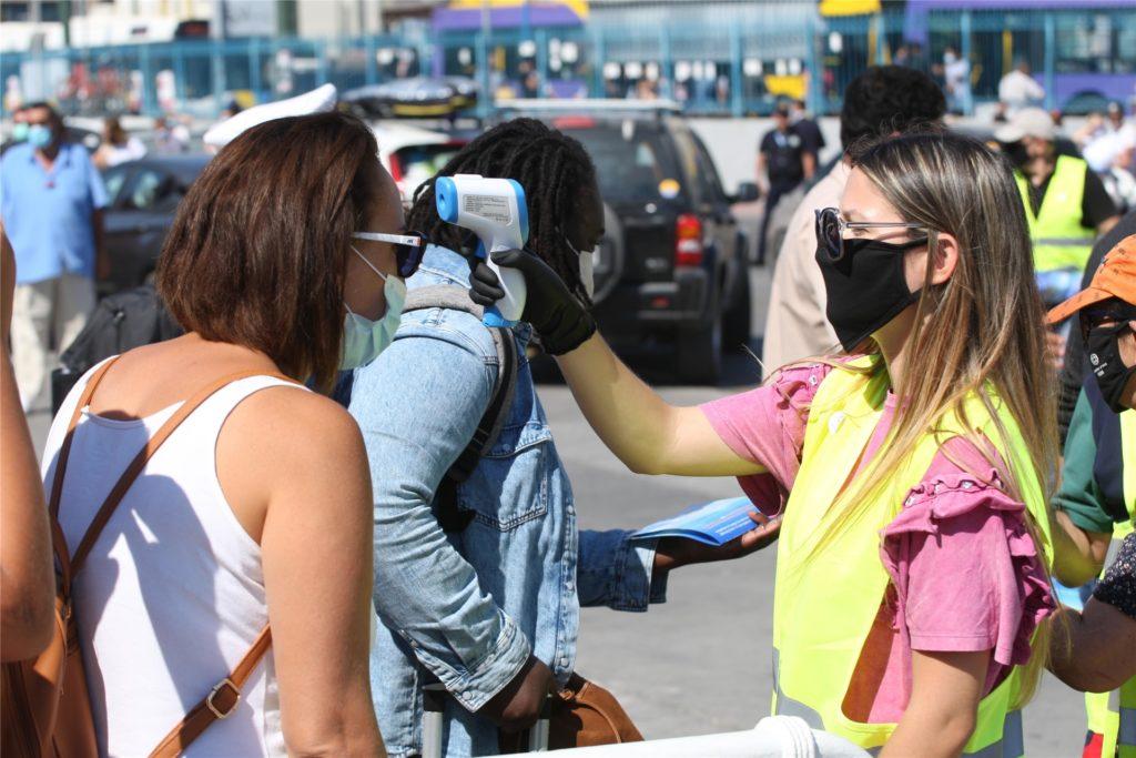 Im Hafen von Piräus wird beim Verlassen einer Fähre die Temperatur einer Reisenden gemessen. Die griechische Regierung hat auch für die Urlaubsregion der Halbinsel Chalkidiki und die Insel Mykonos neue Einschränkungen angeordnet.