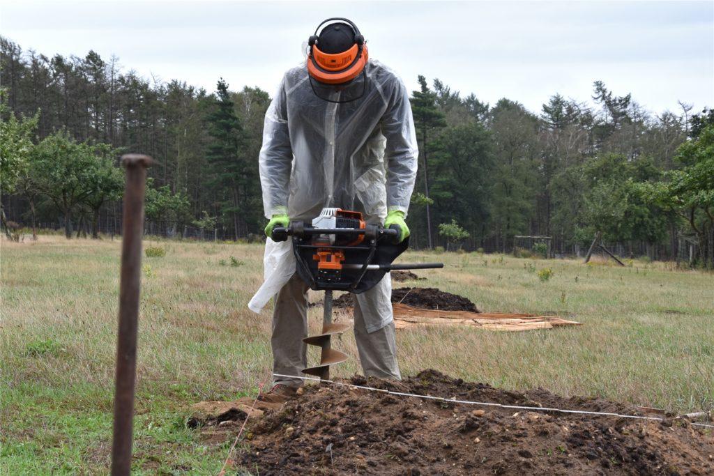 Steffen Müller bereitet die Löcher für die Holzpfähle vor.