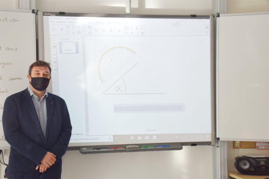 Knut Kasche steht vor einer digitalen Tafel. Diese kommen an der Paulus-van-Husen-Schule seit drei Jahren zum Einsatz.