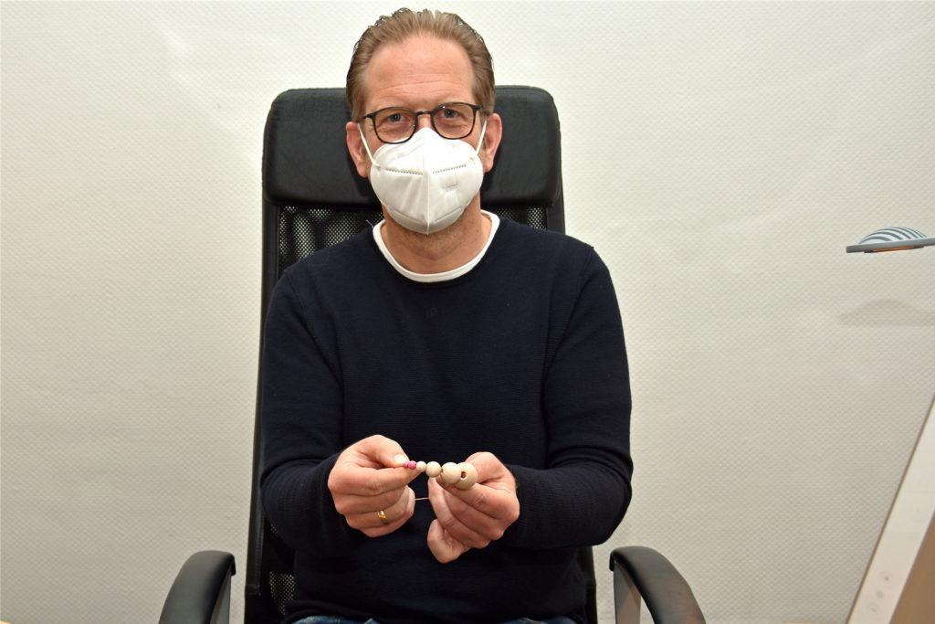 Frauenarzt Thorsten Rosen zeigt anhand der Holzkugeln, was die Taktile Untersuchung leisten kann. Die pinken Kügelchen können Ärzte nicht ertasten, die Medizinisch-Taktilen-Untersucherinnen hingegen schon.
