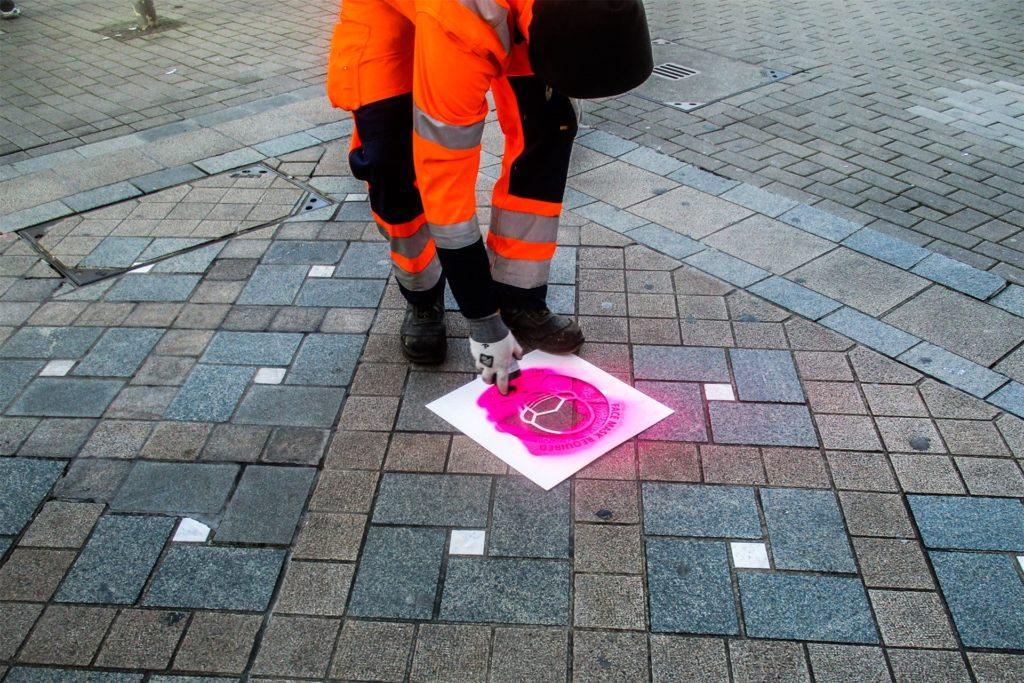 Die aufgesprühten Piktogramme sollen an die Maskenpflicht in der Innenstadt erinnern.