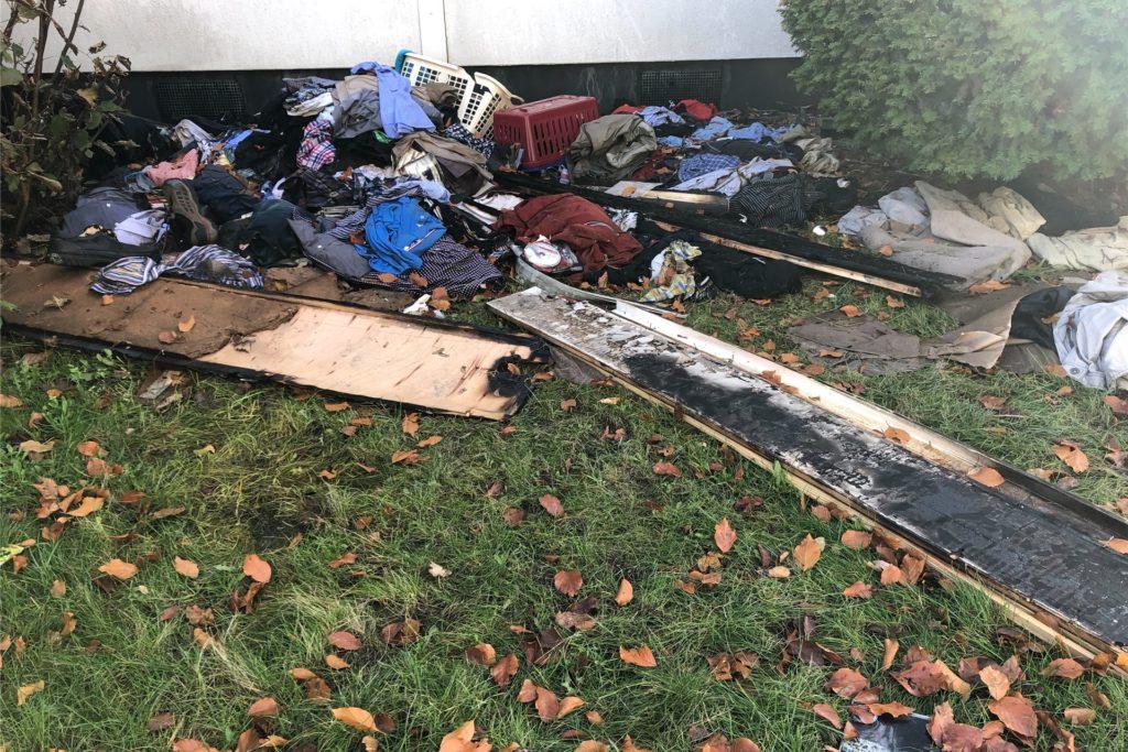 Verbrannte und verkohlte Kleiderüberreste und Sachspenden liegen neben der Eingangstür.