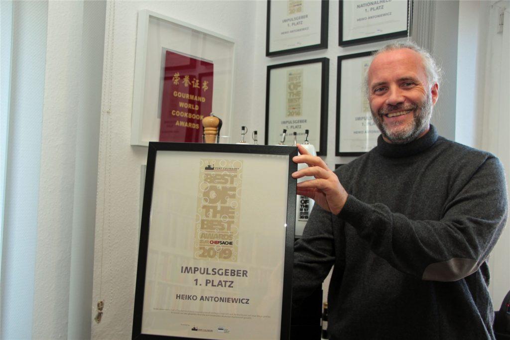 Der bekannte Koch zeigt eine seiner vielen Auszeichnungen.