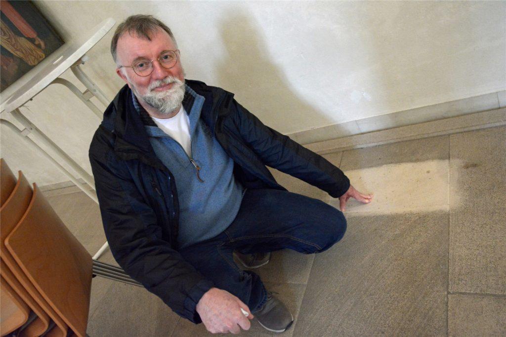 Pfarrdechant Jürgen Schäfer zeigt den Boden in der Kirche St. Christophorus. Der stark verschmutzte Sandstein bekommt nun eine Schönheitskur. Nach 13 Jahren ist der Farbunterschied deutlich zu erkennen.