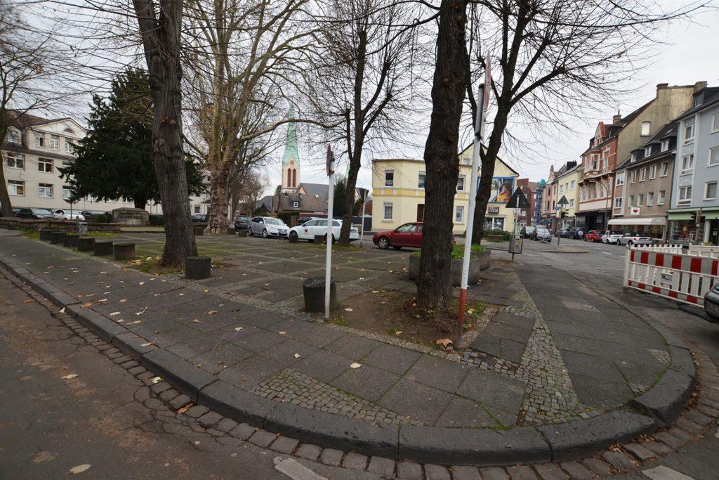Der Platz zwischen Adalmundstraße (links), Jonathanstraße (im Hintergrund) und Mengeder Straße (rechts) soll Passanten zum Aufenthalt einladen. Die Stadt will elf neue Bäume pflanzen - allerdings auch fünf alte Bäume fällen.