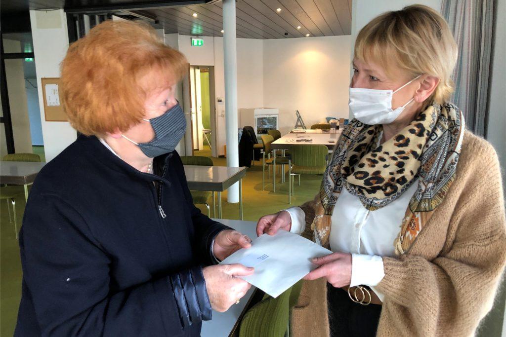 Gemeindemitglied Marion Hugo überreicht Pfarrerin Kerstin Hanke ihre selbst gebastelten Sterne