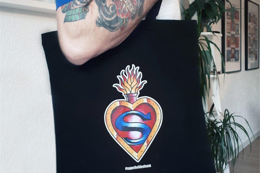 Eine Baumwolltasche mit einem aufgedruckten Herz kann in drei im Text genannten Geschäften für zehn Euro gekauft werden.