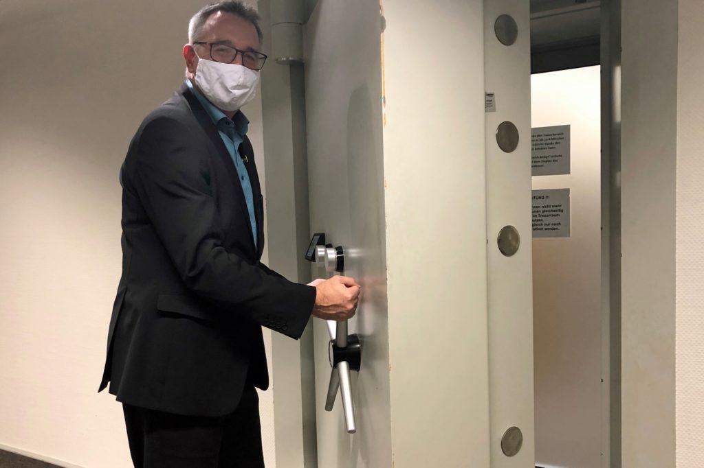 Rainer Kruck, Direktor für den Marktbereich Castrop-Rauxel der Sparkasse, zeigt, wie dick die Tür zum Kundentresorraum ist.