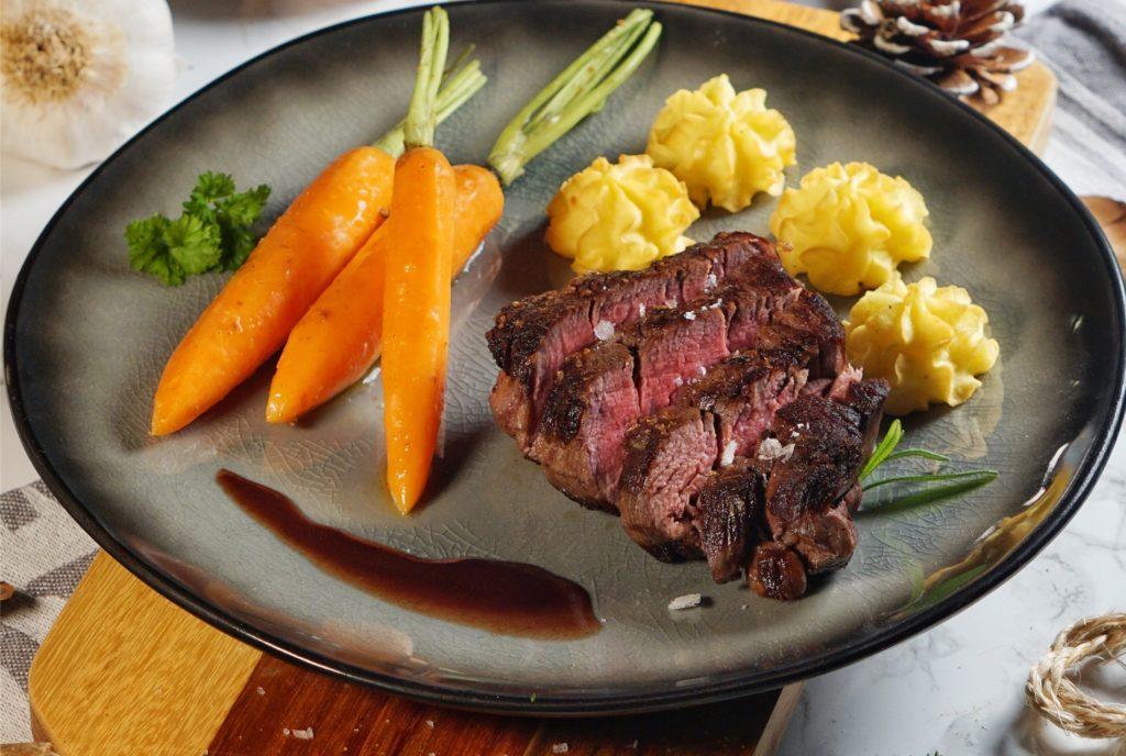 Das Hauptgericht des Weihnachts-Menüs: Rinderfilet an Rotweinsauce mit Herzoginkartoffeln und glasierten Kardamom-Möhren.