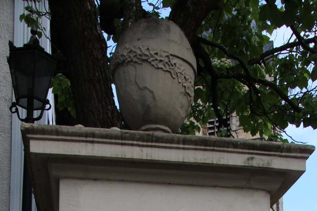 Auf dem Ehrenmal steht ein ovales Gefäß, das an eine Urne erinnert und von einer Efeuranke umwickelt ist.