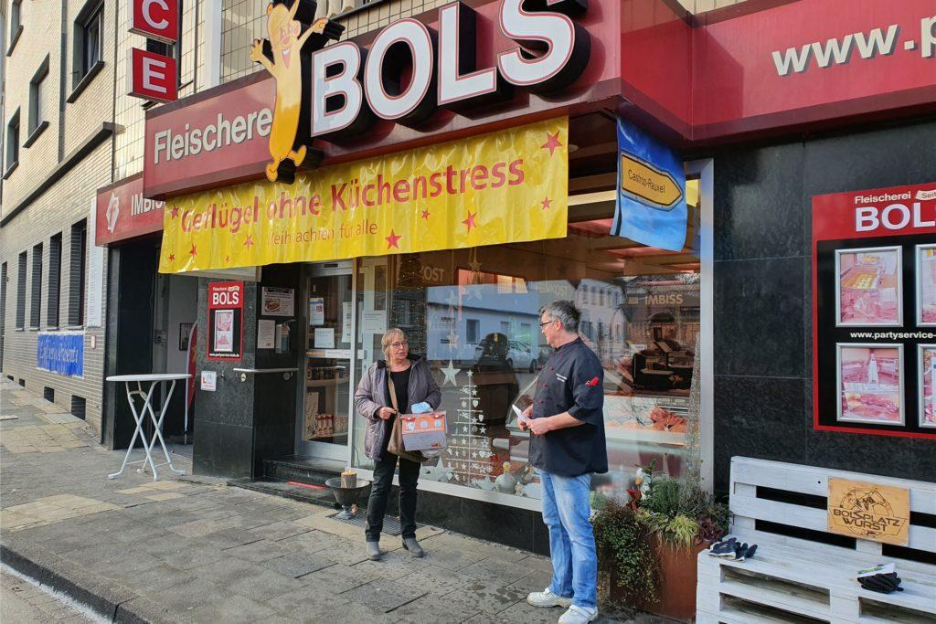 Kundin Ellen Broos-Marr erhält einen der ersten Papierbehälter von Fleischermeister Willi Bols.