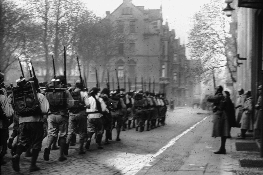 Die Fassade im Hintergrund steht heute noch. Kai Schäder hat, zusammen mit der Transfer-Buchhandlung, auch eine Tour zum Thema Ruhrbesetzung angeboten. Nach der Pandemie wird diese wahrscheinlich wieder aufgenommen.