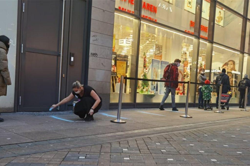 Eine Mitarbeiter zieht vor dem Müller weitere Abstandstreifen, falls noch mehr Kunden kommen sollten.