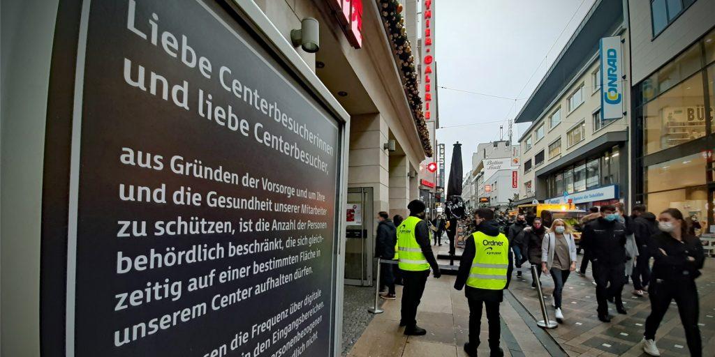 Ein Schild weist am Haupteingang der Thier-Galerie in Dortmund auf die Einlass-Beschränkungen hin.