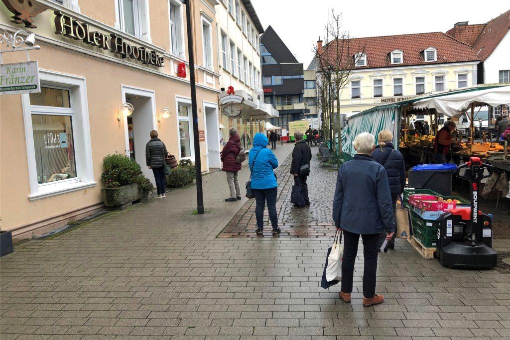 Wartende Menschen vor der Adler-Apotheke am Markt.