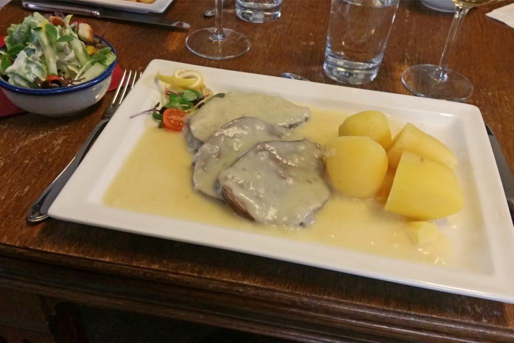 Das Rindfleisch mit Zwiebelsoße, Kartoffeln und gemischtem Salat