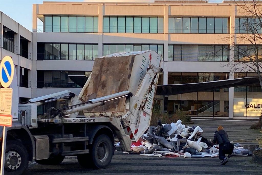 Ein Lkw kippt einen Container mit Schaufenster-Puppen und Reklametafeln vor der Karstadt-Filiale ab.
