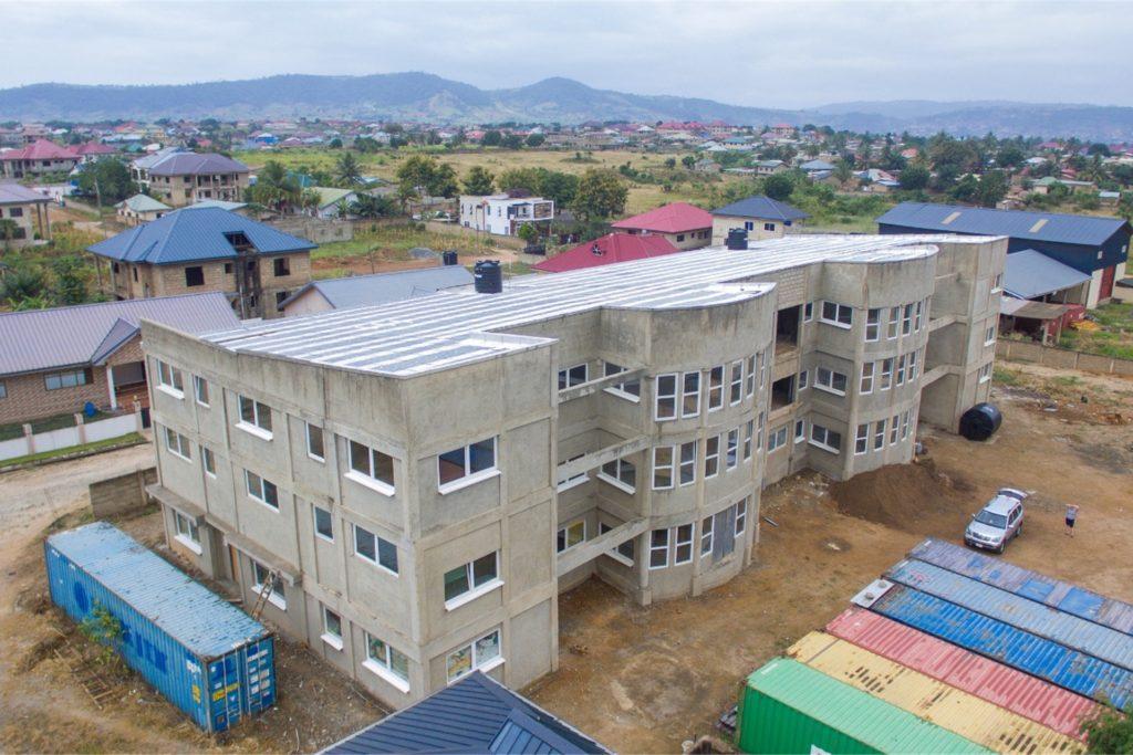 Ein Luftbild vom Krankenhausgebäude. Ein Großteil des dort verbauten Materials wurde von Deutschland aus mit Seecontainern (links) dorthin verschifft.