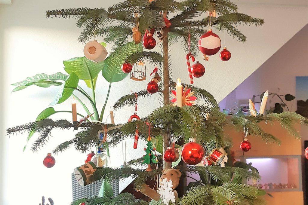 Kugeln mit Masken und eine Klopapier-Rolle aus Keramik ergänzen an diesem Baum von Jeanette Willms den Weihnachtsschmuck.