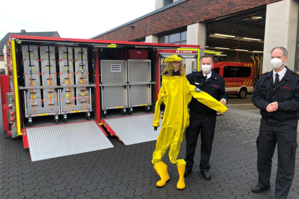 Kreisbrandmeister Stefan van Bömmel (links) und hat am Mittwoch den Dekontaminationscontainer und das neue dazugehörige Wechselladerfahrzeug vorgestellt. Zur Ausrüstung gehören 34 Gebläsefilteranzüge für insgesamt 40.000 Euro. Einen davon zeigt der stellvertretende Stadtlohner Feuerwehrchef Carsten Kuglarz.