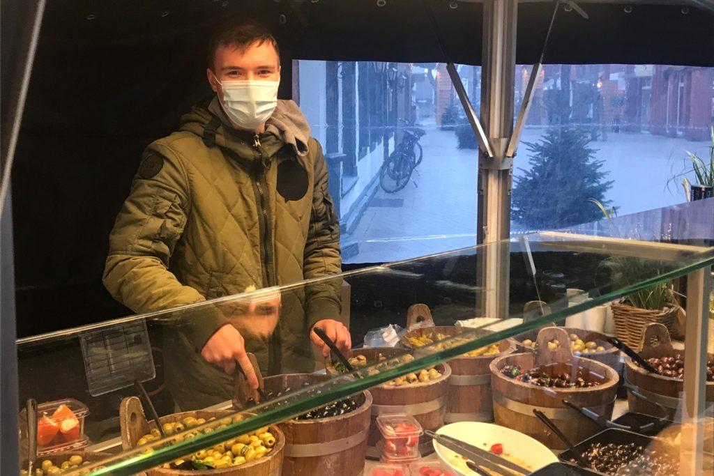 Ein Mitarbeiter von Bramers Feinkost verkauft Oliven, Antipasti und Käsecremes – besonders beliebt an den Feiertagen.