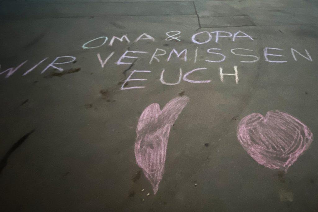 """""""Oma und Opa wir vermissen euch"""" steht auf einer Straße mit Kreide geschrieben. Durch deutlich härtere Corona-Einschränkungen haben viele Enkelkinder ihre Großeltern nicht mehr besucht, die im Heim leben."""