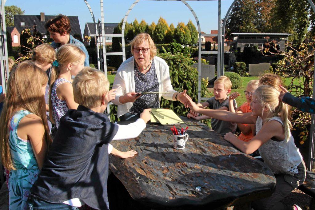 Auch Hospizarbeit, die durch die Corona-Pandemie nicht mehr möglich ist: Renate Barenbrügge (M.) mit Kindern im Friedhofsgarten